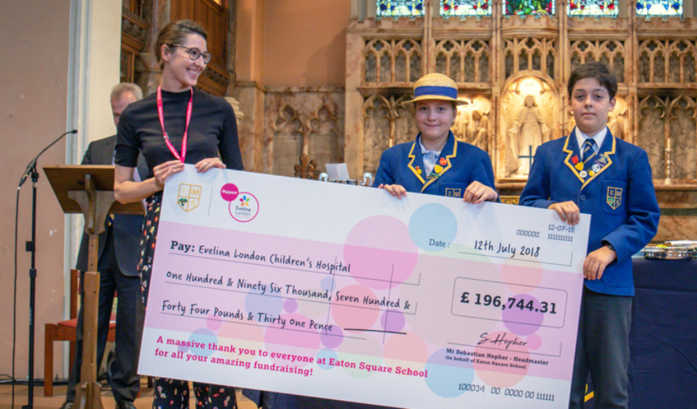 a woman, becky from fundraising department, and two pupils wearing blue school uniforms holding a big check in front of them with evelina logo on it and sum written of £196,744.31