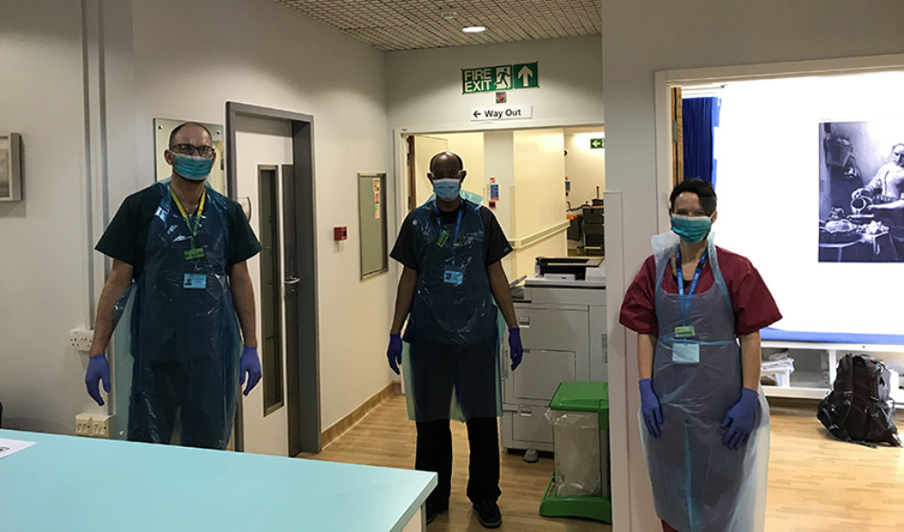 Three members of staff in PPE standing in a corridor of the hospital