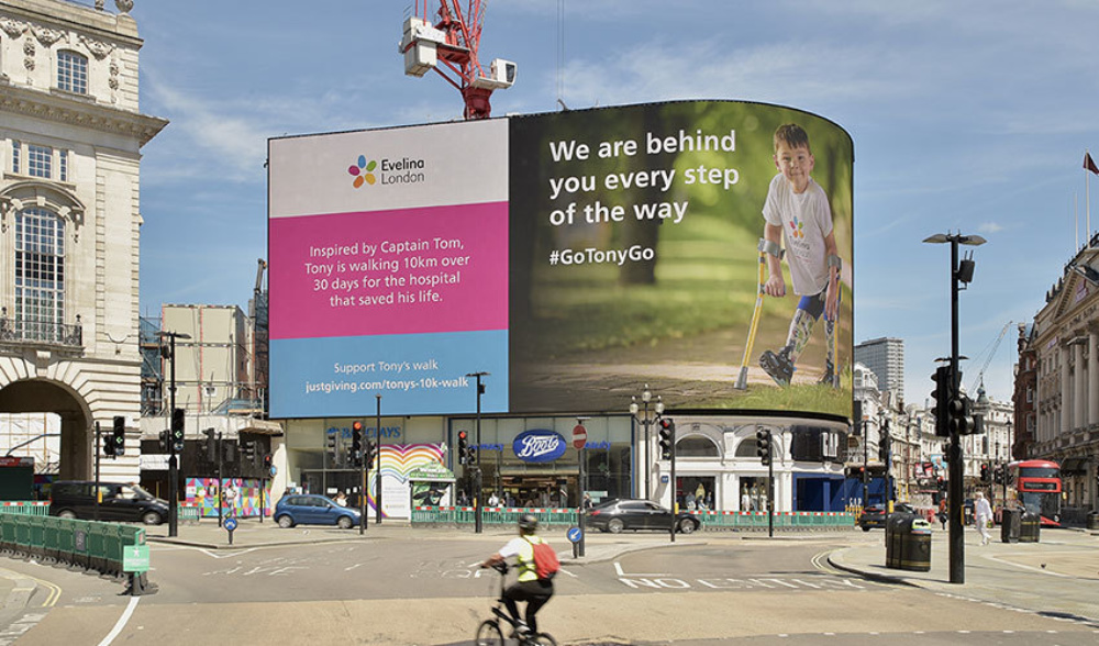 A large outdoor sign of a young boy, walking in the park with crutches and smiling in an Evelina London t-shirt