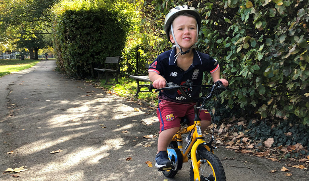 Young boy in football strip, wearing a helmet on a bike, cycling through the park