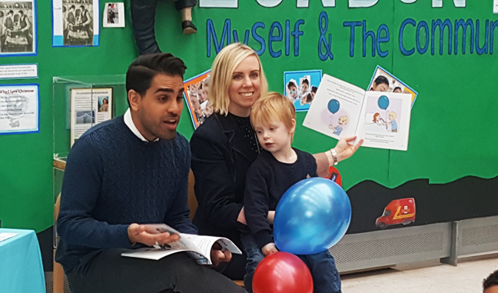 man and woman with a boy on her laps and red and blue balloons reading books