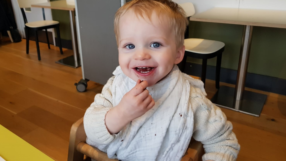close up of a two year old boy smiling, in the kitchen