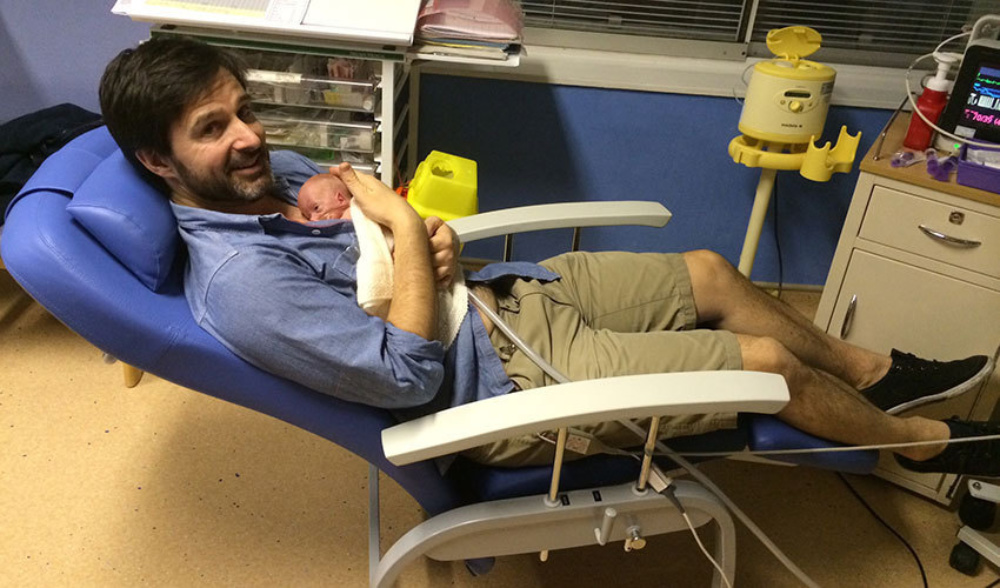 Parent enjoying reclining chair with the newborn baby