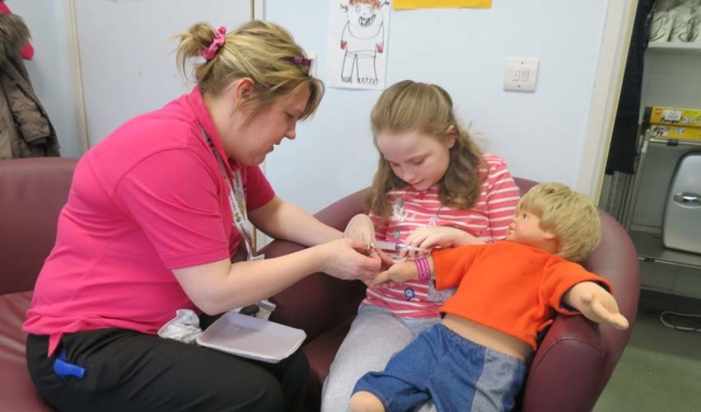 Lucy learning about blood tests with Cathy and Charlie Doll