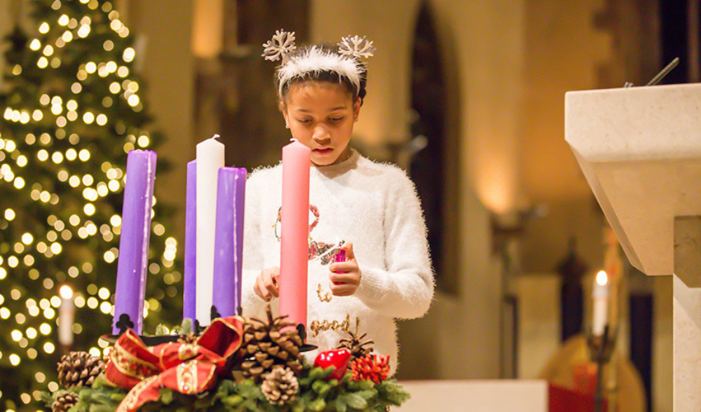 A young girl stood in front of three candles in a church lighting them