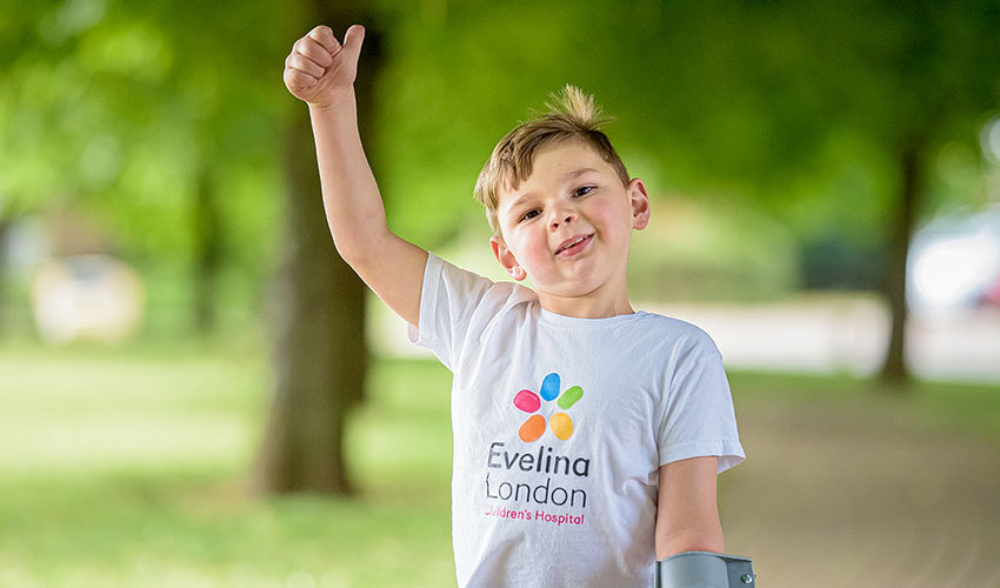 Close up of a young boy in an Evelina London t-shirt, with his thumbs up, while on a crutch.